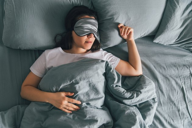 Woman asleep in bed with a mask over her eyes