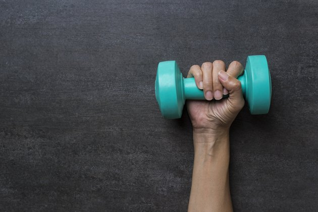 woman hand holding green dumbbell on black background