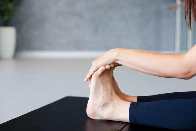 Young woman is practicing yoga. Girl is meditating and sitting on mat in lotus pose indoors. Sport workout in gym.