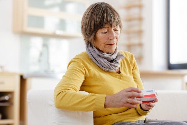 Senior woman reading label on medicine