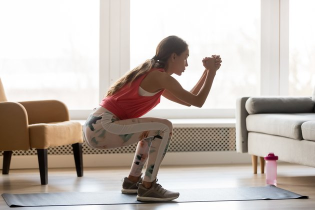 woman doing squat at home for body-weight strength training