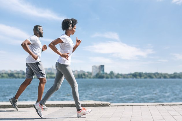 Smiling Afro Spouses Jogging Along River Bank In City