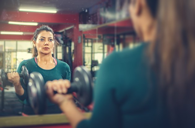 Woman doing dumbbell workout in a gym to build bigger biceps
