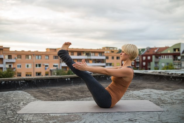 Woman Doing Yoga-Boat Pose/Navasana on a Rooftop