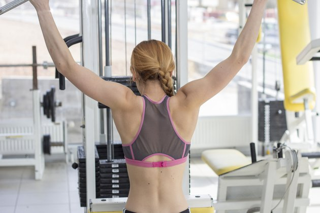 Female working out on lat pulldown machine