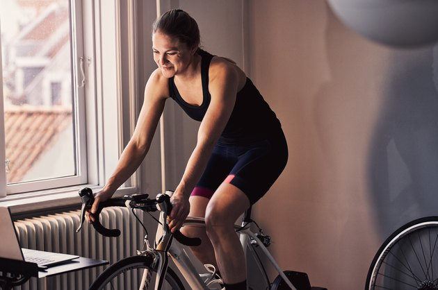 Woman using an indoor cycling trainer to get health benefits of biking indoors
