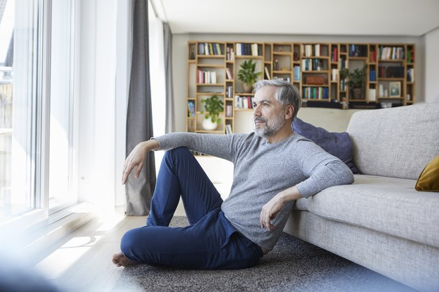 Mature man sitting on floor of his living room looking out of window