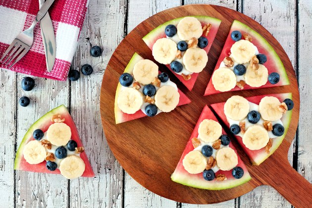 Watermelon pizza with bananas, blueberries and yogurt on serving board