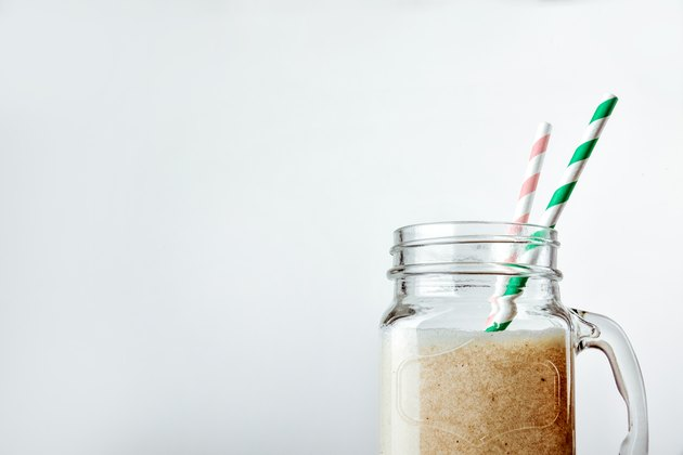 Protein cocktail with milk, vanilla in a glass jar with straws. Sports nutrition