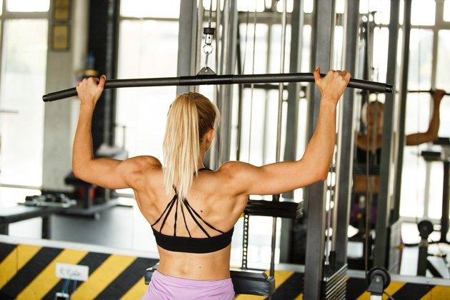 Muscular woman doing lat pulldowns