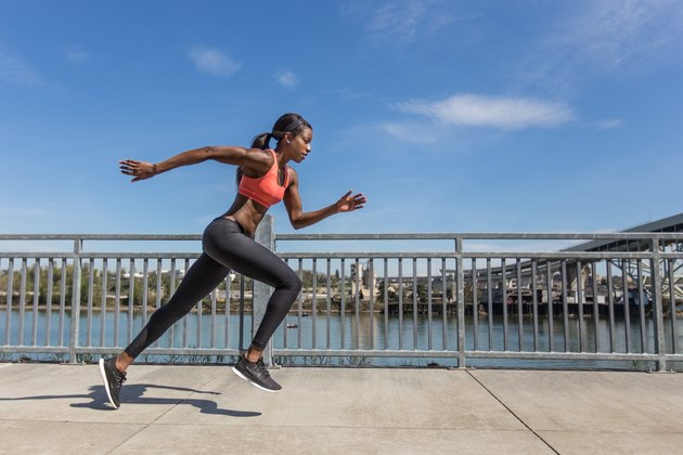 Attractive ethnic female sprinter training in the city