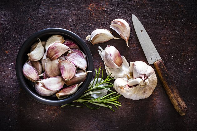 Garlic bulb and cloves shot from above on rustic brown background