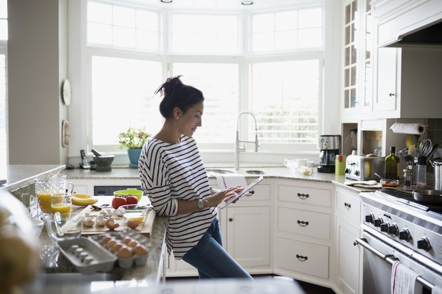 Woman using myWW app on digital tablet to prepare a recipe in kitchen