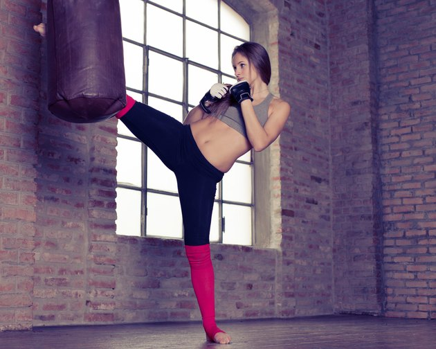 woman kick the heavy bag