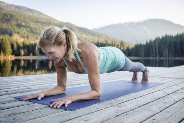 Senior woman doing plank on dock near lake during sunset.