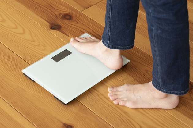 View of a person's feet stepping onto a bathroom scale