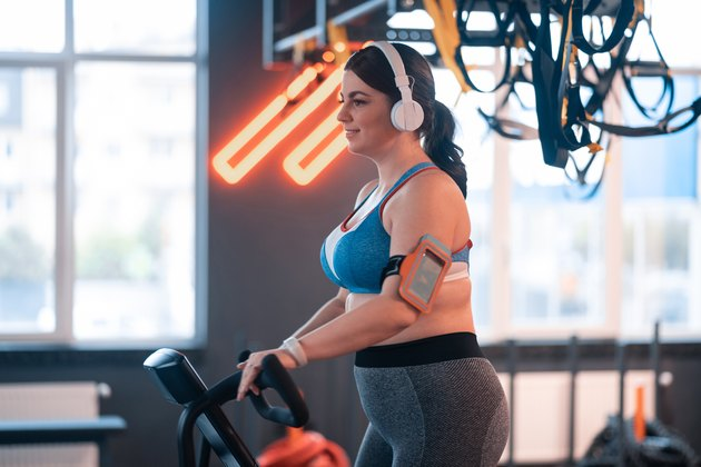 Woman cycling in gym and listening to music in earphones
