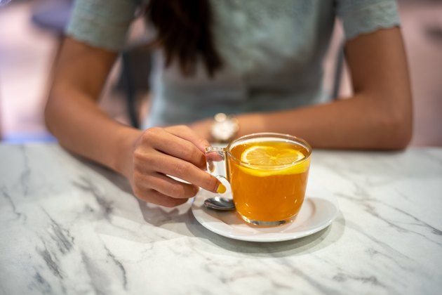 Young asian woman's hand holding a cup of hot lemon tea on top of marble table