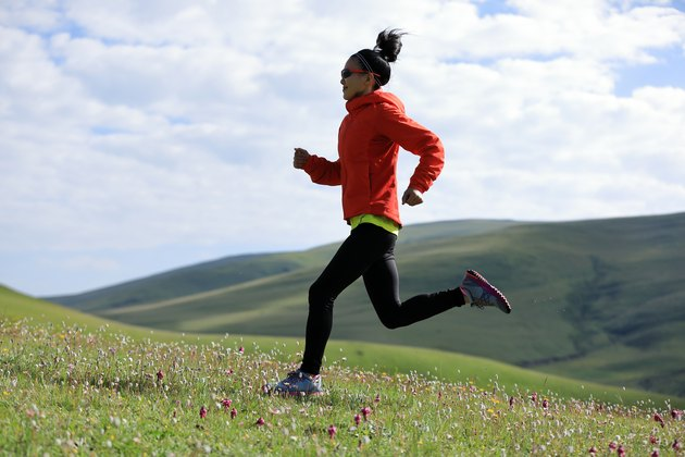 Woman ultramarathon trail runner running  on grassland mountain