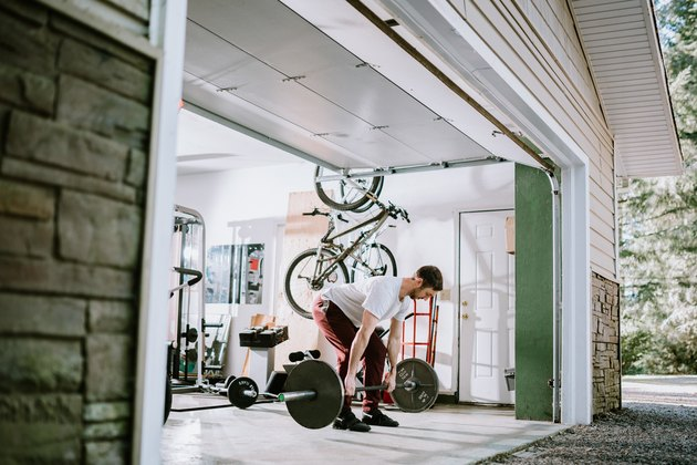 Man lifting barbell to build muscle in garage