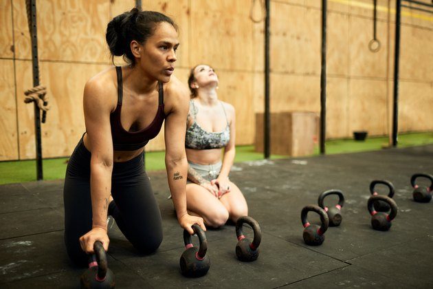 Two hispanic women tired and resting after doing a long series of push-ups.