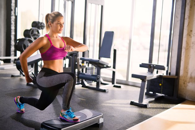 Woman doing lunges on step aerobics equipment at gym.
