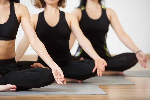 Young women in yoga class, relaxing meditation lotus pose. Copy space. Healthy lifestyle and fitness club. Cropped view