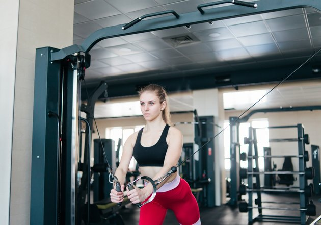 Young fit woman doing exercise in crossover machine at gym