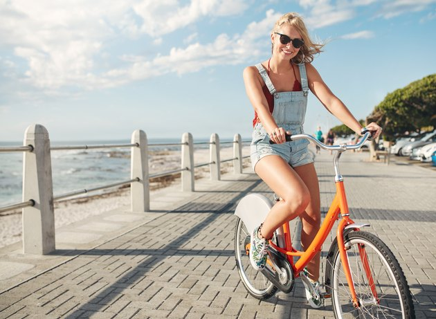Beautiful young woman riding bicycle on seaside road