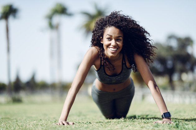 Happy sporty young woman doing push-ups on lawn