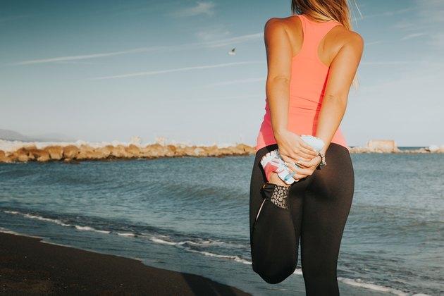 Woman leg stretching at the beach.