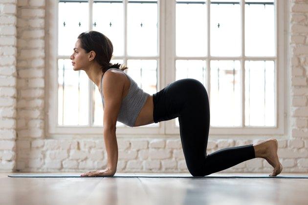Woman practicing yoga Cow Pose, Bitilasana in studio