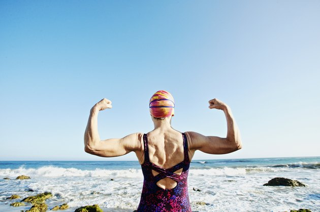 Older Caucasian woman flexing her upper body muscles on beach