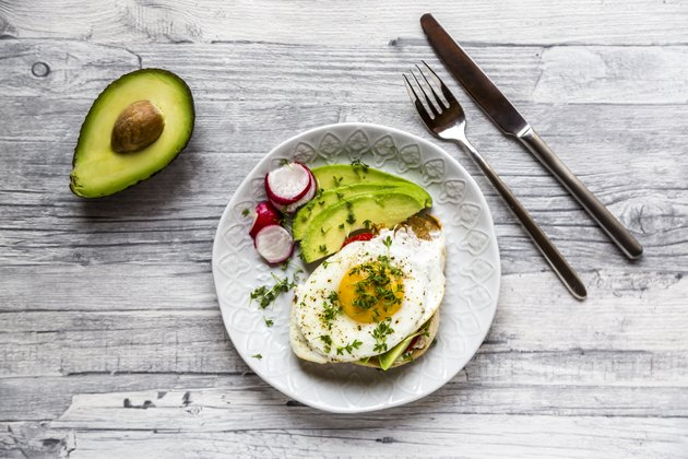 Toast with fried egg, avocado, red radish, tomato and cress