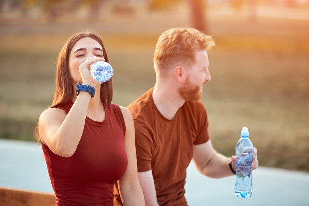 Couple making pause in an urban park during jogging or exercise drinking water