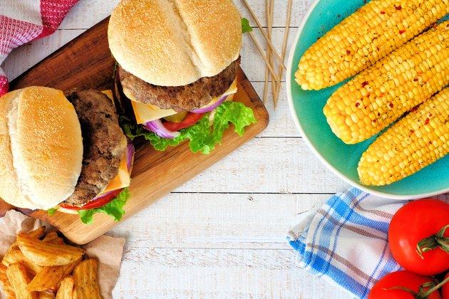 Picnic scene with hamburgers, corn and potato wedges