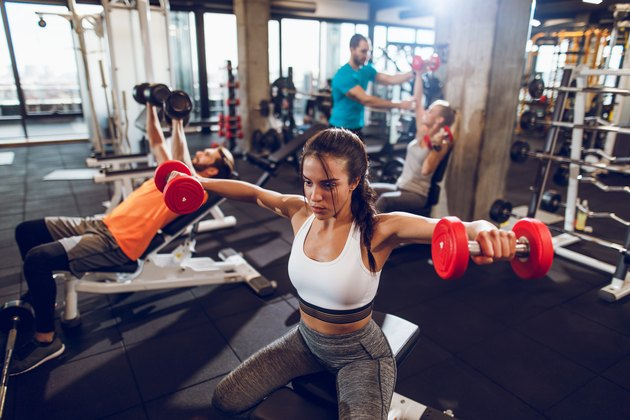 Young sporty woman doing dumbbell exercise at the gym