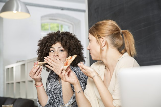 Two colleagues in office eating pizza