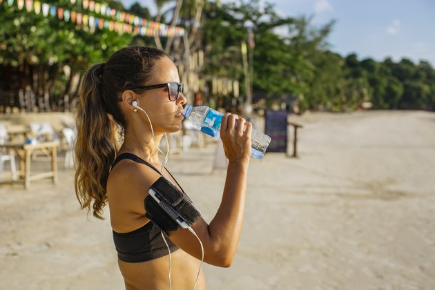 Woman drinking water on the beach and listening to her summer workout playlist