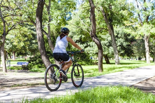 Woman riding bycicle at the park. Rear view