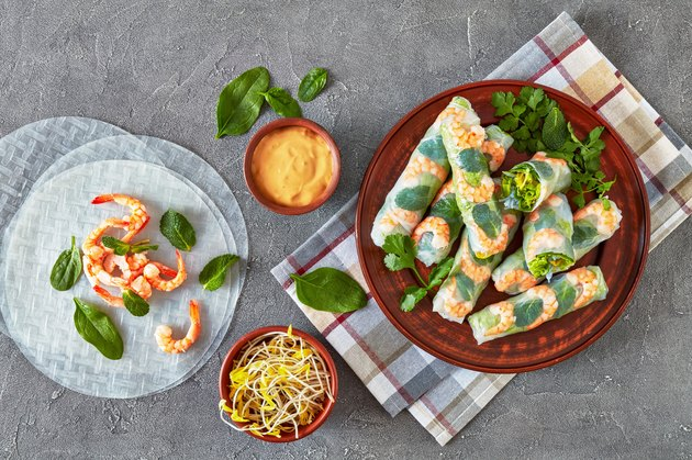 raw Asian spring rolls of rice paper with shrimps, rice noodle, lettuce and mint fillings
