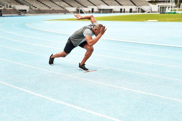 Black man sprinting outside on blue track