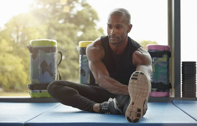 man doing static seated hamstring stretch
