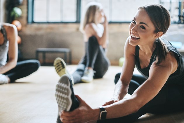 A smiling woman stretching after a workout