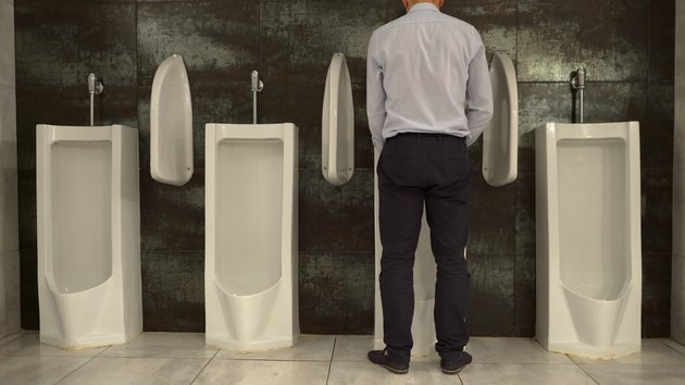Man Peeing in Urinal in the Restroom
