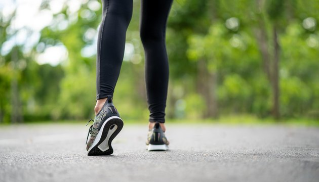 Runner feet running on road closeup on shoe. Young fitness woman runner athlete running at road. Athlete runner feet running on road closeup on shoe. Woman fitness sunrise jog workout wellness concept