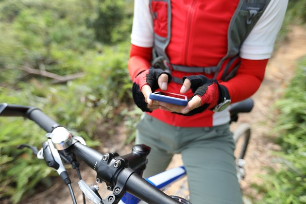 Cyclist on hill holding mobile phone using cycling gloves