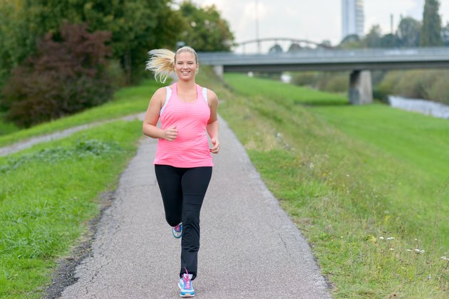 Blonde smiling woman running along river