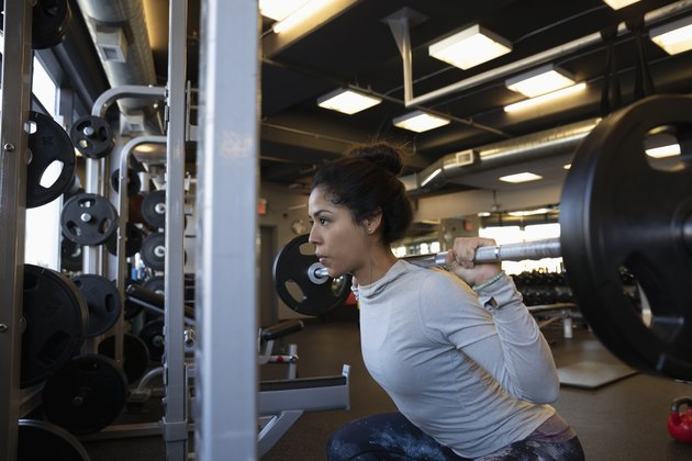 Focused woman doing barbell squats in gym