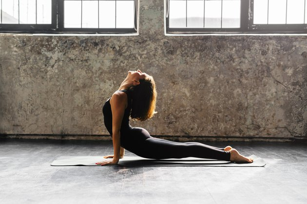 Young woman practicing yoga in urban loft: Upward Facing Dog